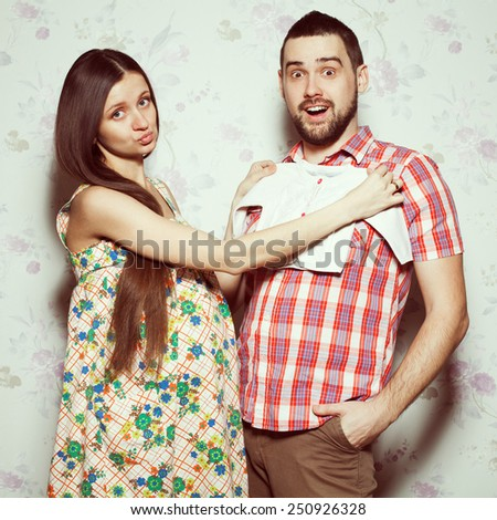 Stylish pregnancy concept: portrait of funny couple of hipsters (husband and wife) in trendy clothes (shirt, dress, jeans) holding small size baby shirt. Vintage (retro) style. Studio shot - stock photo