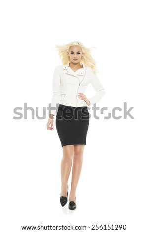 Stylish pretty blond woman with her hair blowing in a breeze posing with her hand on her hip in a trendy white jacket and black skirt, isolated on white - stock photo