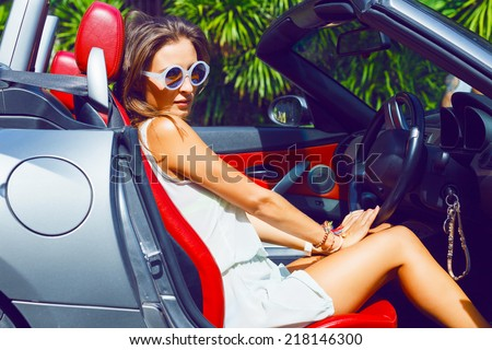 Stylish pretty tan woman riding luxury cabriolet car, enjoy her adventures in sunny day at hot topical country, wearing relaxed beach dress and sunglasses. - stock photo