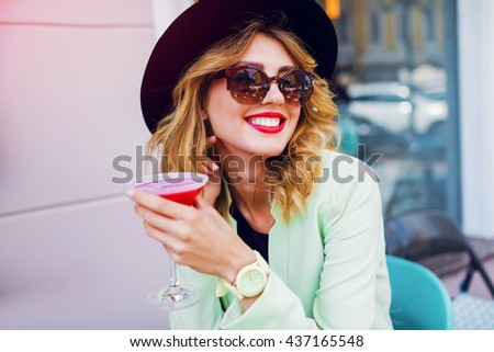 Stylish pretty woman in casual  outfit, black hat and neon jacket drinking sweet tasty beverage. Enjoying her holidays and relax. Bright summer colors. Positive mood.  - stock photo