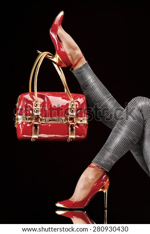 Stylish red bag hanging on a chic high-heeled shoe. - stock photo