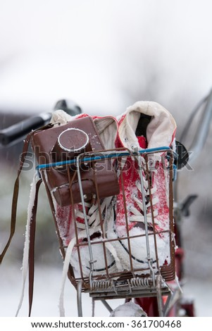 Stylish red sneakers and cameras snowy snow in a basket by the vintage bicycle - stock photo