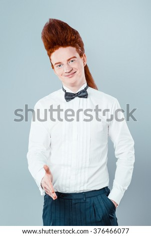 Stylish redheaded young man with bouffant on head. Boy wearing shirt with bow-tie, proposing to shake hands and looking at camera