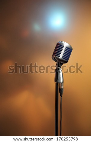 Stylish retro microphone on a colored blurred  background - stock photo