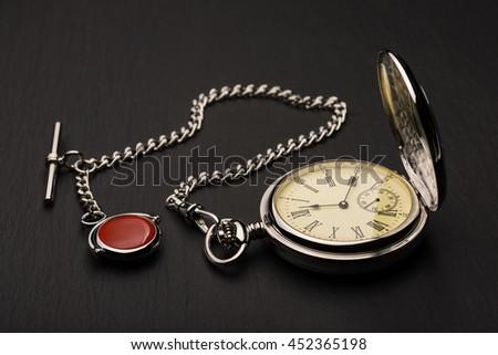 Stylish retro pocket watch on black slate - stock photo
