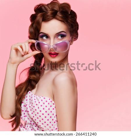Stylish retro style beautiful woman wearing polka dot dresss and sunglasses. Over pink background - stock photo