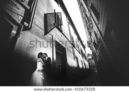 Stylish rich adorable bride and groom kissing on the streets of Rome Italy on a sunny day black and white - stock photo