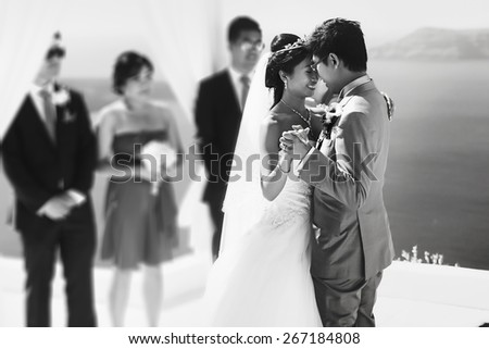 stylish rich asian bride and groom dancing first wedding dance in island Santorini greece sunshine black and white - stock photo