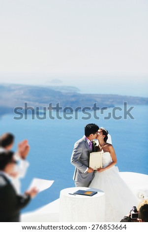 stylish rich smiling asian bride and groom  wedding kissing in island Santorini greece sunshine