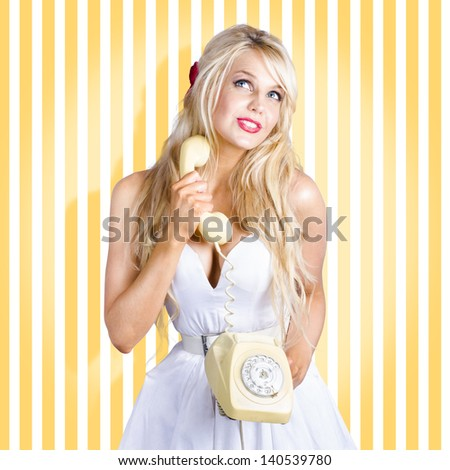 Stylish 1950s pin-up girl wearing retro white denim dress while chatting during an old fashion phone conversation. Retro fashion concept - stock photo