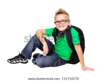 Stylish schoolboy with bag and headphones sitting on the floor - stock photo