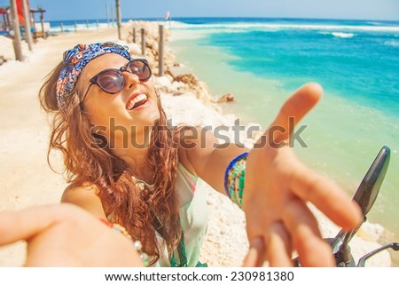 stylish selfie with own mobile phone on a beach while riding a motorbike - stock photo