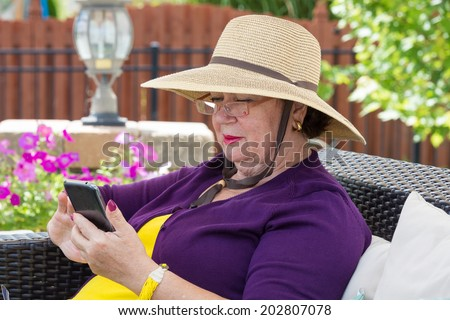 Stylish senior lady using a smartphone as she sits in a comfortable chair in the sunshine on her patio in a wide brimmed sunhat - stock photo