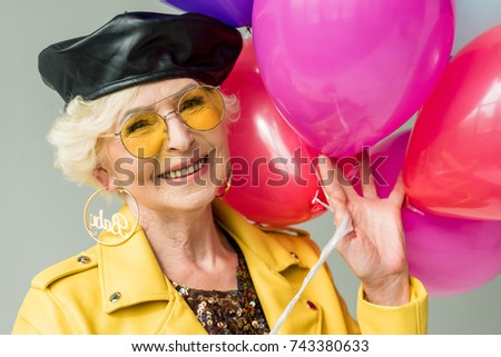 stylish senior woman in yellow jacket with colorful balloons, isolated on grey