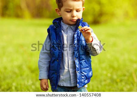 Stylish serious baby boy with ginger (red) hair in trendy striped shirt and blue jacket standing in the park and holding dandelion. Hipster style. Sunny weather. Copy-space. Outdoor shot - stock photo