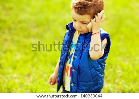 Stylish serious baby boy with ginger (red) hair in trendy t-shirt & blue jacket standing in the park and talking to his mother on mobile phone. Hipster style. Sunny weather. Copy-space. Outdoor shot - stock photo
