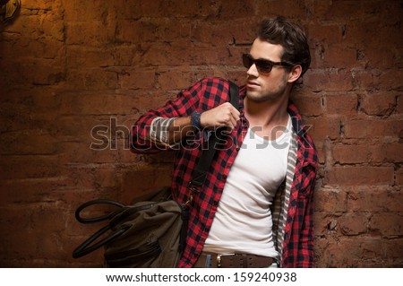 Stylish sexy man looking away. With handbag on his shoulder  - stock photo