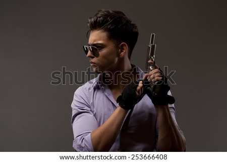 stylish shooter or contractor with gun, glasses gloves and big hair - stock photo