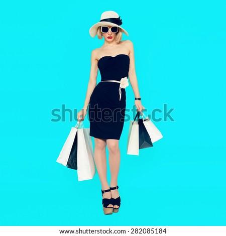 Stylish Shopping Lady with shopping bags on blue background - stock photo
