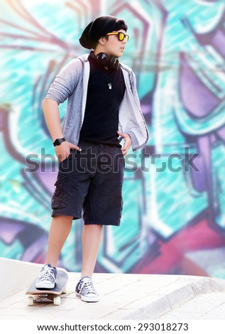 Stylish skater boy listening music standing outdoors on beautiful graffiti wall background, active teen life, hipster style, fashion lifestyle
