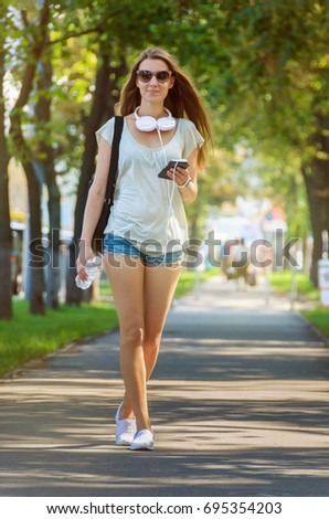 stylish slender girl student walks along a city street with a mobile phone in her hands and headphones around her neck, a lovely hot sunny day? street look