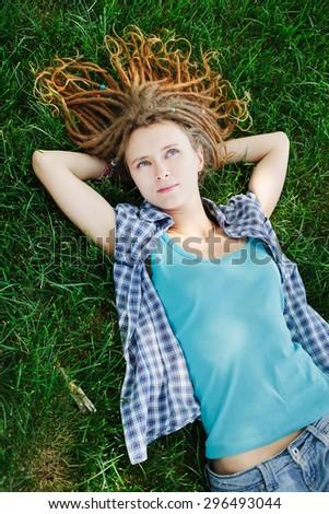 Stylish slim girl with dreadlocks lying on green grass - stock photo