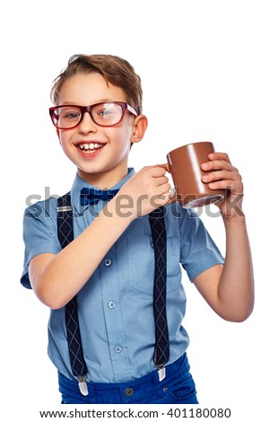 Stylish small boy in glasses holding cup of tea, coffee or juice. He is smiling and looking into the camera. Isolated on a white background. - stock photo