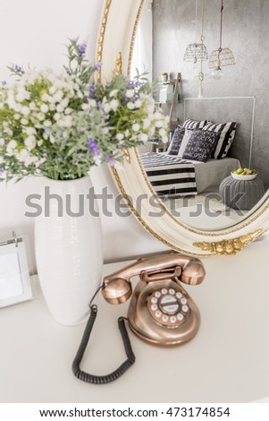 Stylish small telephone, vase of flowers and round mirror lying on a white bedroom commode