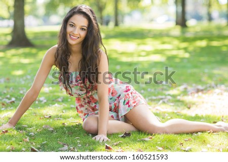 Stylish smiling brunette sitting on grass in a park on a sunny day