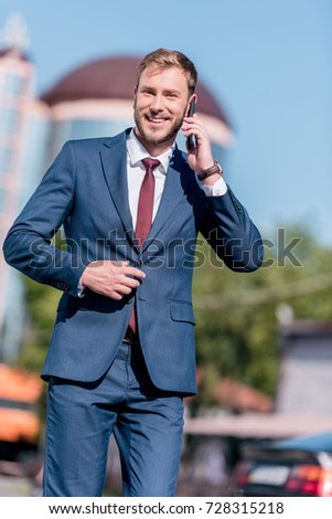 stylish smiling businessman in suit using smartphone