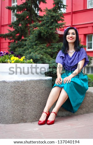 Stylish smiling young woman sitting on bench in park near flowerbed and red building on background. - stock photo