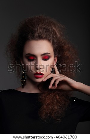 Stylish styling hair, bright makeup. Portrait girl which lowered her eyes.  - stock photo