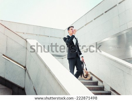 Stylish successful businessman goes up the stairs