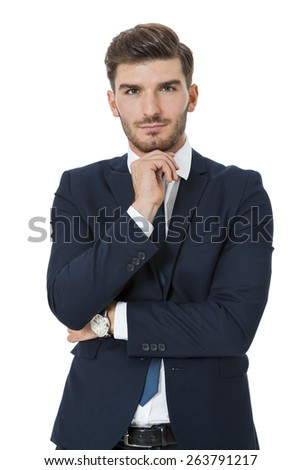 Stylish successful handsome young businessman standing in a relaxed pose with his hands in his pockets and his suit jacket open, isolated on white
