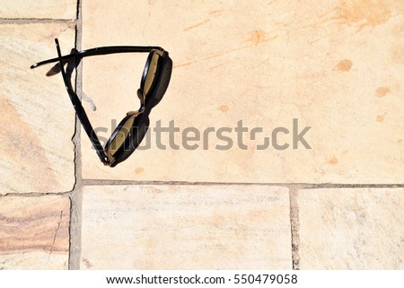 Stylish sunglasses isolated on a tile pool deck on a sunny day