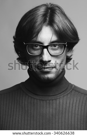 Stylish teacher, lecturer concept. Portrait of smiling young handsome man wearing eyeglasses over gray background. Trendy polo neck. Perfect long glossy hair. Yves Saint Laurent style. Indoor shot