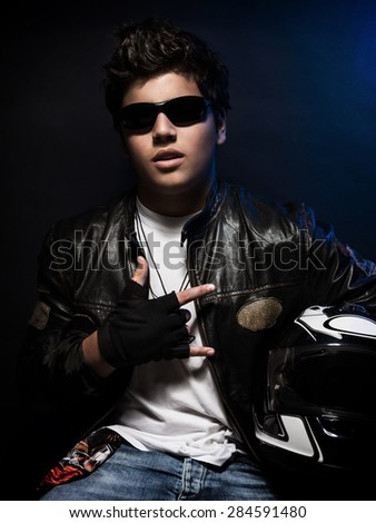 Stylish teen biker portrait, nice boy wearing fashion leather jacket and sunglasses holding in hands helmet over dark blue background