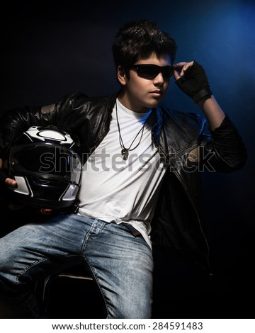 Stylish teen boy biker sitting and posing in the studio over dark blue background with helmet in hands, fashion for motorcyclist