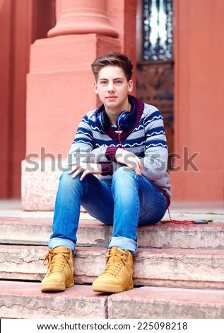 stylish teenage boy with headphones, sitting on stairs - stock photo