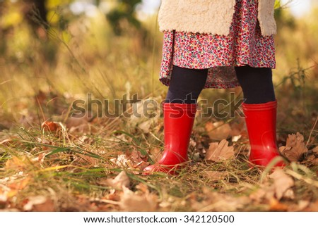 Stylish toddler in red boots - stock photo
