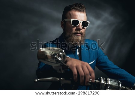 Stylish trendy man wearing modern sunglasses and a formal suit sitting waiting on a motorcycle, frontal view - stock photo