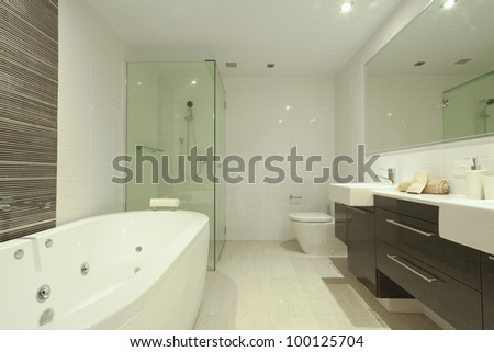 Stylish twin bathroom with two sinks, mirror, shower, toilet and round bathtub. - stock photo
