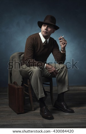 Stylish vintage 1940 business man smoking cigarette sitting on chair in room. - stock photo