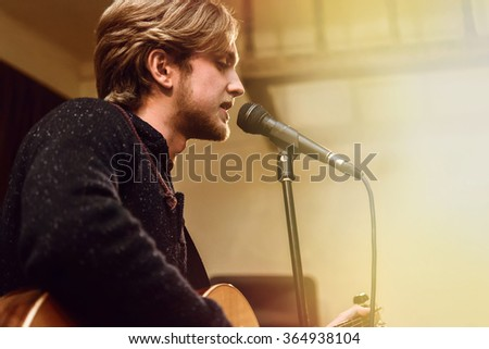 stylish vocalist with beard performing lyrical song on stage with his band - stock photo
