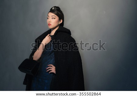 Stylish wealthy asian woman in retro forties fashion with handbag. Standing against wall. - stock photo