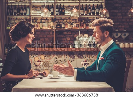 Stylish wealthy couple having desert and coffee together in a restaurant. - stock photo