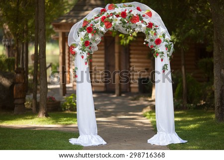 stylish wedding arch with red roses and white lilies, garden, wedding ceremony