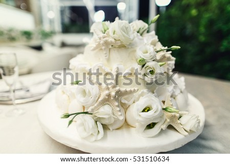 Stylish wedding cake decorated with silver seastars and white flowers