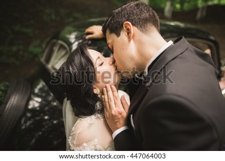 Stylish wedding couple, bride, groom kissing and hugging near retro car in autumn