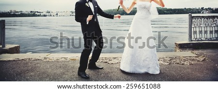 Stylish wedding couple dancing by the lake.